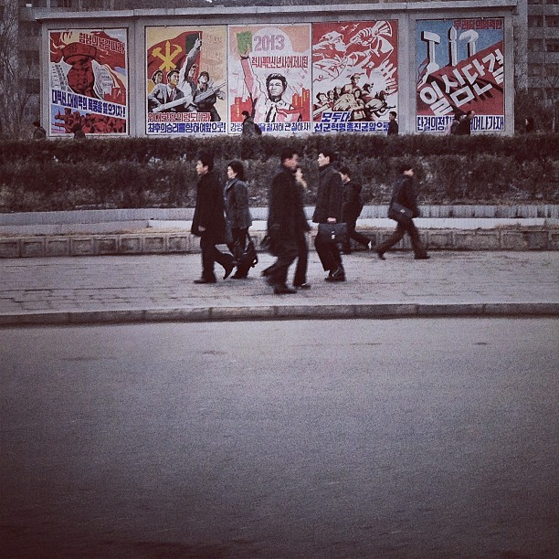 """North Korean commuters pass by propaganda posters in #Pyongyang."""