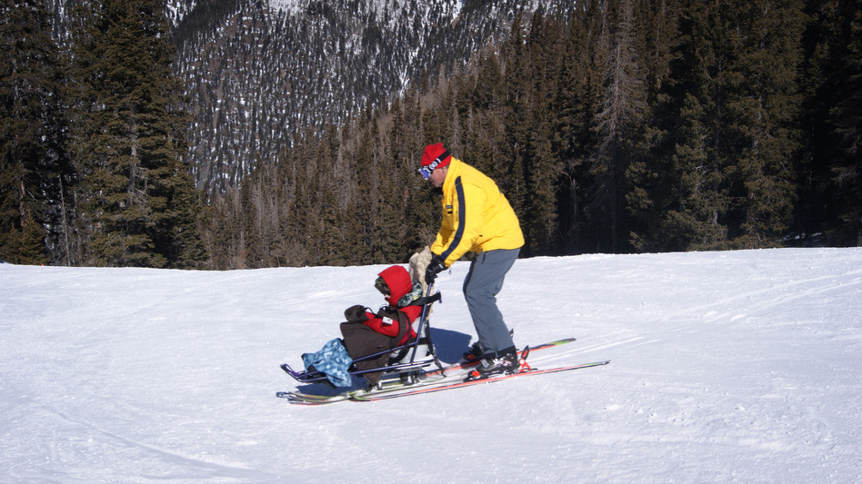 Tilghman Logan and his instructor, Craig Stagg, do some practice turns using sit skis. Some ski resorts have created opportunities for people with disabilities to participate in snow sports. (KUNM)
