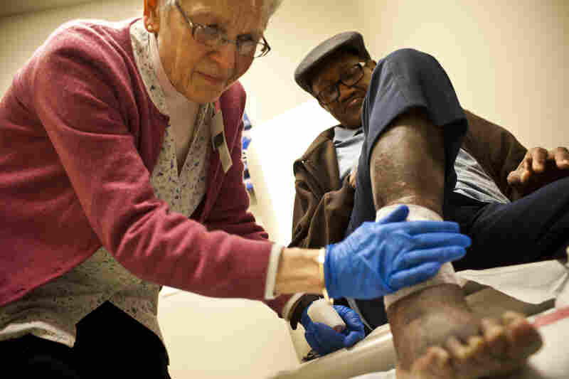 HCH also runs a convalescent floor in a nearby shelter where patients can recover from fractures or recent surgeries. Susan Zator, a community nurse for more than 41 years, bandages 66-year-old William Jones' foot injury. Zator says this service is vital for homeless men and women who cannot recover properly while living on the street.