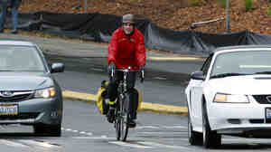 "Washington State Rep. Ed Orcutt has apologized for saying  ""the act of riding a bike results in greater emissions of carbon dioxide from the rider,"" after an email with a bike shop owner sparked criticism. Here, a cyclist rides in Seattle last year."