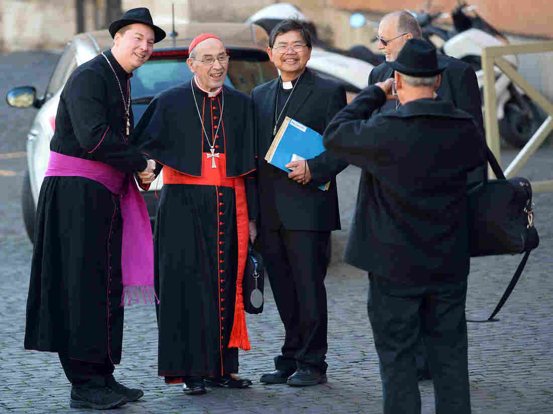 That's not a real bishop on the left: A man later identified as Ralph Napierski of Germany (at left) posed with Cardinal Sergio Sebiastiana and others on Monday at the Vatican. Napierski was an imposter. He was later escorted from the area by Swiss Guards.