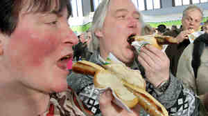 "Visitors eat rostbratwurst sausages at the ""Green Week"" agriculture fair in Berlin in January 2011."