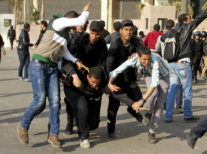 Egyptian policemen arrest an alleged rioter during clashes in Cairo on March 6.