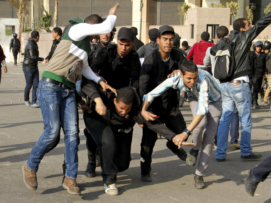 Egyptian policemen arrest an alleged rioter during clashes in Cairo on Wednesday. (APA/Landov)