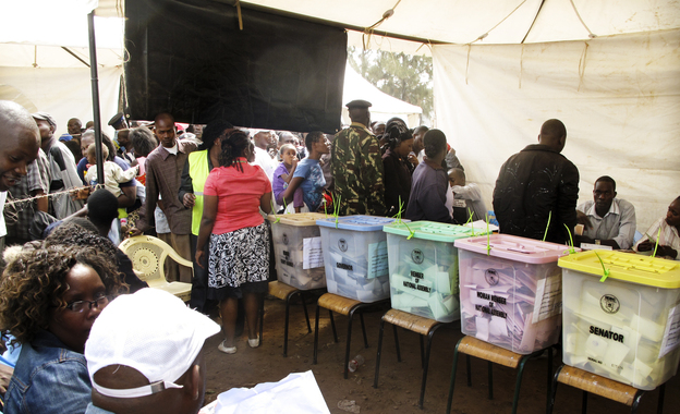 Kenyan election observers and voters in the mixed slum of Kiambiu — where the first fires started in Nairobi after the disputed presidential election of 2007 — vote in this year's elections. Could something as innocent as the color of the ballots and ballot boxes be contributing to voting