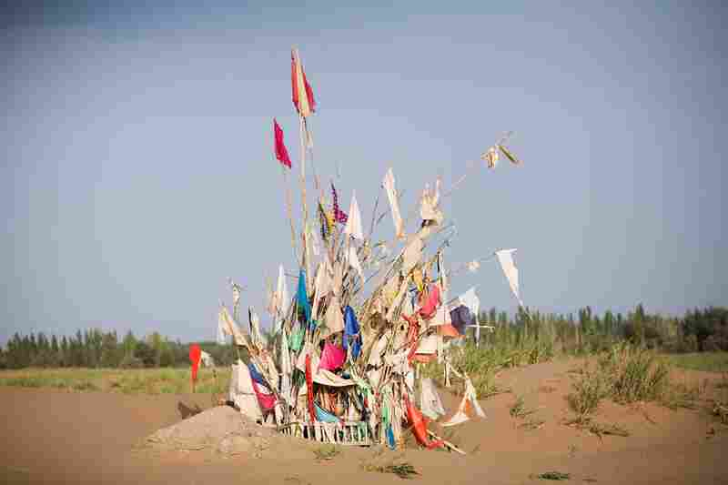 Unrevealed, Site 3 (Harvest Prayers), 2010. Markers for saints in the desert are maintained by shaykhs, who dig out the sands that would otherwise cover them over time. The number of flags on a marker correlates to a saint's power at performing miracles.