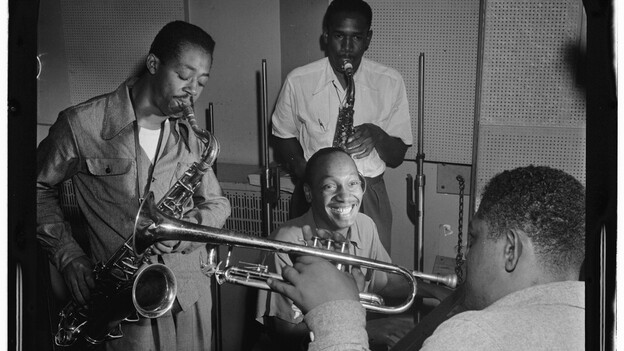Tadd Dameron (smiling at center) was an important figure in American jazz and bebop. He is shown here with Fats Navarro on trumpet, and Charlie Rouse and Ernie Henry on saxophone. (Library of Congress)