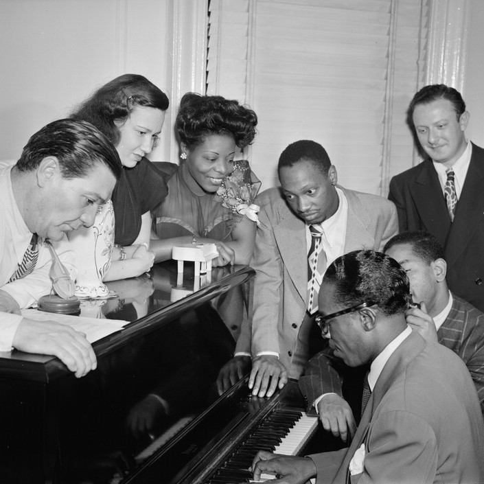Tadd Dameron (standing fourth from the left) watches Hank Jones play piano at the apartment of Mary Lou Williams (third from left) in this 1947 photo. Dameron is the subject of a new biography that seeks to revive the reputation of the often-overlooked jazz master.