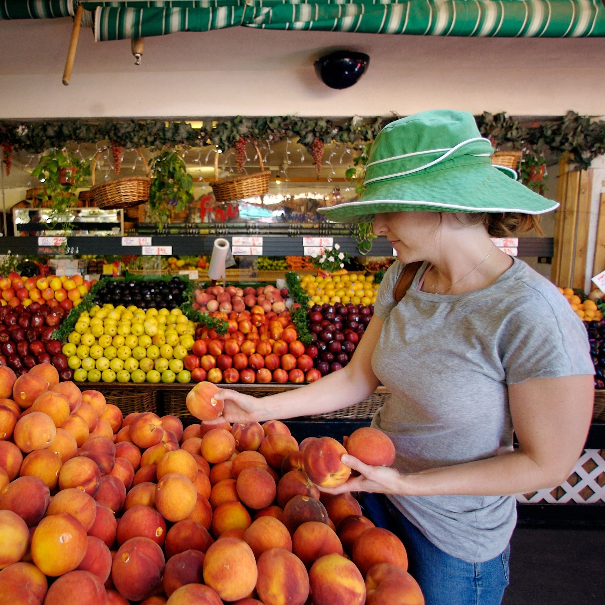 Tara Igoe shops for sweet California peaches at a fresh produce stand at the Farmers Market in Los Angeles, August 2007.
