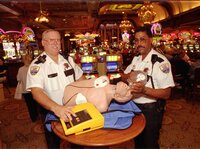 Main Street Station casino security staffers Jim Daugherty (left) and James Boles show off an automated external defibrillator in Las Vegas in 1997. Back then, the idea of putting the devices in casinos to save lives seemed like a long shot.