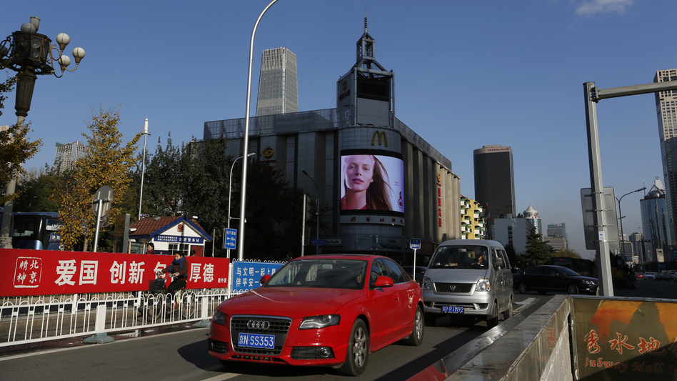 As much as $2.34 trillion in yearly income goes unreported in China, an economics scholar says. Here, an imported car passes a shopping mall in Beijing.