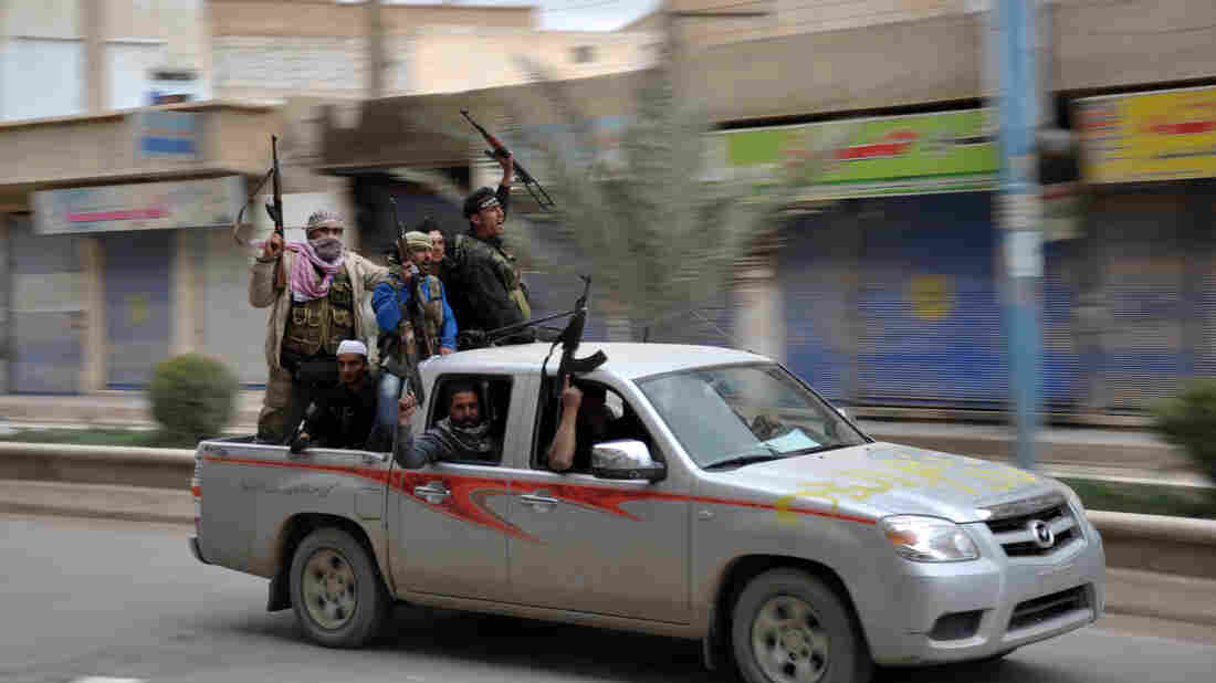 Syrian rebels celebrate in a street in the northeastern Syrian city of Raqqah after capturing the provincial capital on March 4. The government has responded with air strikes, creating a new wave of refugees.