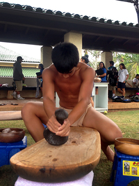 A youth creates poi via ku'i, a process in which taro roots are crushed by stone.