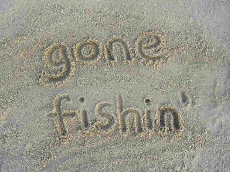 """Gone Fishin'"" written in sand."