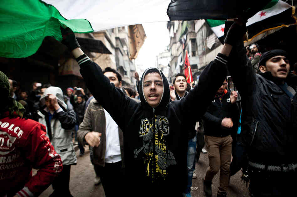Syrians carry a large revolution flag and chant slogans during a protest in Aleppo, Syria, where young people and children sang songs against President Bashar Assad and the Syrian regime, Dec. 21, 2012.