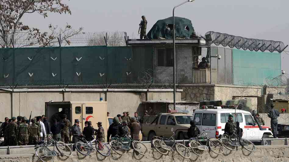 Afghanistan National Army soldiers and security personnel walk at the site of a suicide attack next to the Ministry of Defense main gate in Kabul on Saturday.