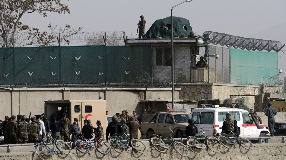 Afghanistan National Army soldiers and security personnel walk at the site of a suicide attack next to the Ministry of Defense main gate in Kabul on Saturday. (Massoud Hossaini/AFP/Getty Images)