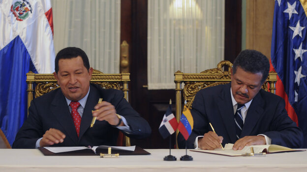 Venezuelan President Hugo Chavez and Leonel Fernandez, the president of the Dominican Republic, sign an agreement in 2010. The Dominican Republic gets abou
