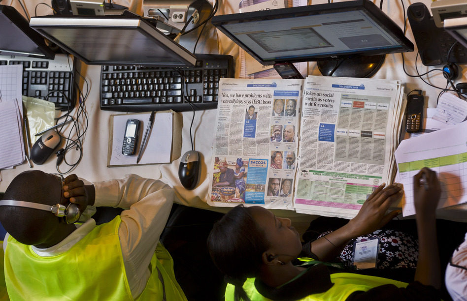 An electoral worker at the National Tallying Center reads a newspaper headlining the problems in the vote counting and tallying process in Kenya this week. Election officials had to count the ballots from the nation's presidential election by hand after abandoning the electronic tabulation system.