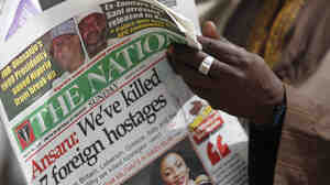 A man in Kano, Nigeria, reads a local newspaper Sunday that carries a story about the killing of seven hostages by a militant group.