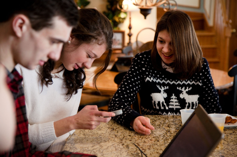 Joseph, Alexandra and Samantha Grimaldo sit around the kitchen counter in the family's home in Marlborough, Mass., playing with Samantha's voice app, though they mostly use sign language at home. (Ellen Webber for NPR)