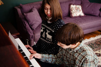 Samantha watches her brother Nicholas play piano. Their mother says that a new customized voice created by researcher Rupal Patel from a young Samantha's voice sample is happy and has a sweetly familiar quality.