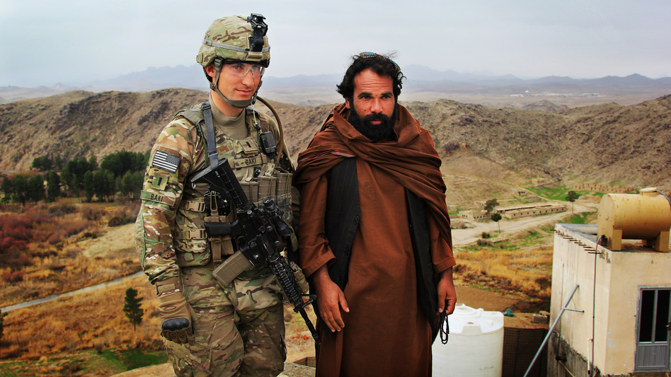 The U.S. military is increasingly focused on helping the Afghan government and security forces become self-sufficient. Here, U.S. Army 1st Lt. Phillip Baki visits with an Afghan police officer, Abdul Karim, at a checkpoint overlooking the Dahla Dam in the southern province of Kandahar. (NPR)