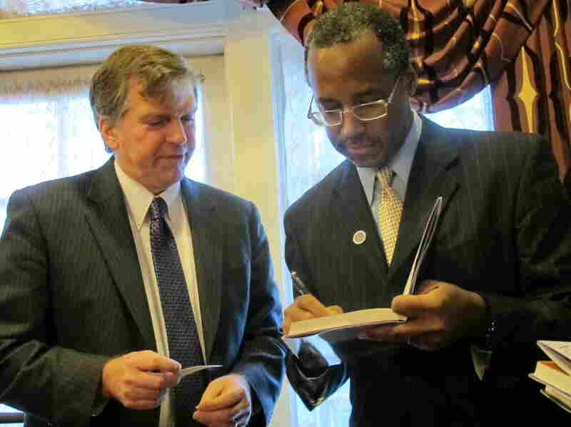 Dr. Ben Carson, right, signs a book for Delegate William Frank in Annapolis, Md., on Friday.