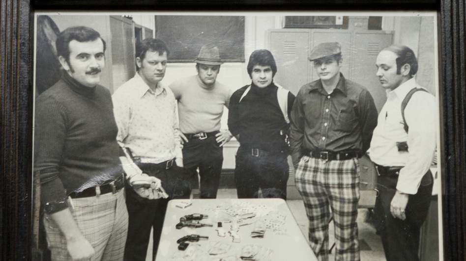 A photo of Richard Piña (fourth from the left) from his days as a Chicago police officer hangs in a waiting area at Rich's Den. (Beth Rooney for NPR)