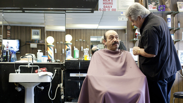 Richard Piña, 69, with customer Augustin Bustos at Rich's Den barbershop in Calumet City, Ill. Piña, who retired from the Chicago police force 12 years ago, works at his shop four or five hours a day. (Beth Rooney for NPR)