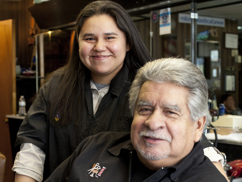 Richard Piña and his youngest daughter, Alex, both work at Rich's Den in Calumet City, Ill. Pina bought the barbershop a few years before he retired from the Chicago police force. (Beth Rooney for NPR)