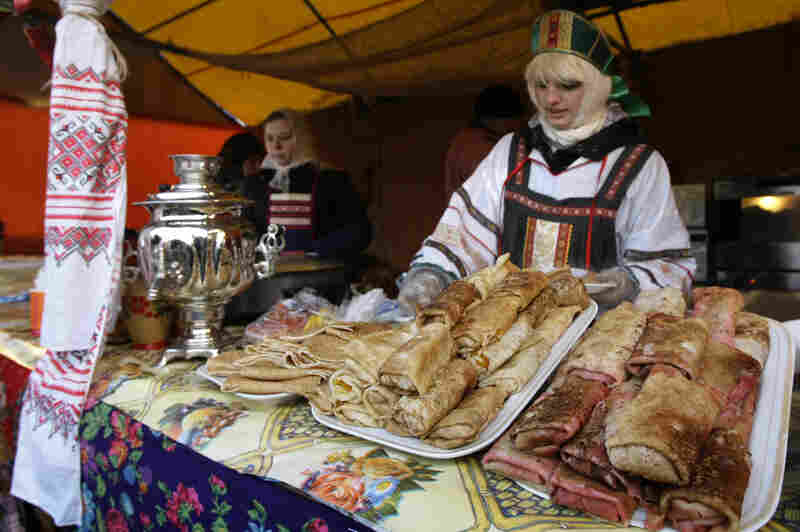 A vendor sells blini at a booth camp just outside the Kremlin in Moscow during Maslenitsa, February 2009. Each day of the week calls for prescribed activities. For example, on Sunday, the final day of the event, people are supposed to seek forgiveness from friends and strangers.