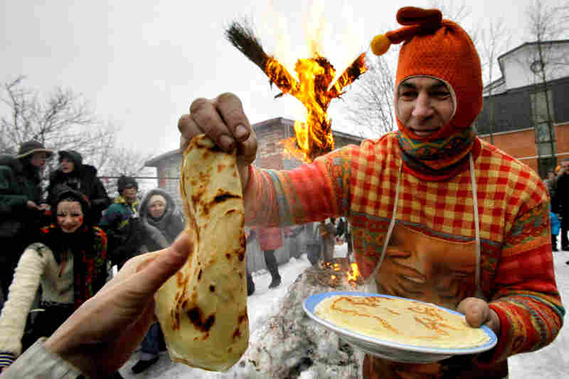 A man dressed as a medieval East Slavic harlequin distributes blini in St. Petersburg, Russia, during the last day of Maslenitsa in 2009. The festival originated in pagan times as a way to mark the end of winter and beginning of spring. Pancakes known as blinis abound: Their round shape and warmth were meant to symbolize the sun.