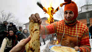 A man dressed as a skomorokh, a medieval East Slavic harlequin, distributes bliny in St. Petersburg, Russia, during the last day of Maslenitsa, March 1, 2009.