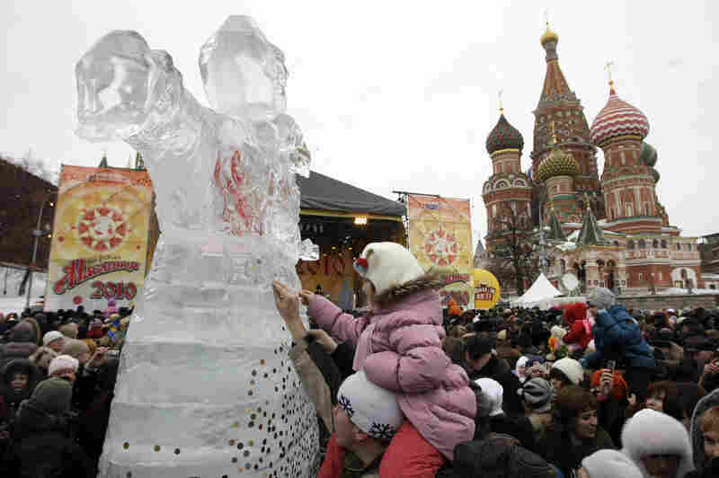 People stick coins to an ice sculpture of Lady Maslenitsa in front of St. Basil's Cathedral just outside the Kremlin on Feb. 14, 2010, during the last day of Maslenitsa celebrations.