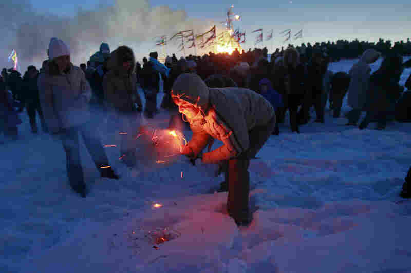 "A man tries to burn a small effigy of Lady Maslenitsa during the final evening of festivities in 2011 in St. Petersburg, Russia. The torching marks the end of the holiday — a fiery goodbye to ""lady winter."" A larger straw effigy burns in the distance."