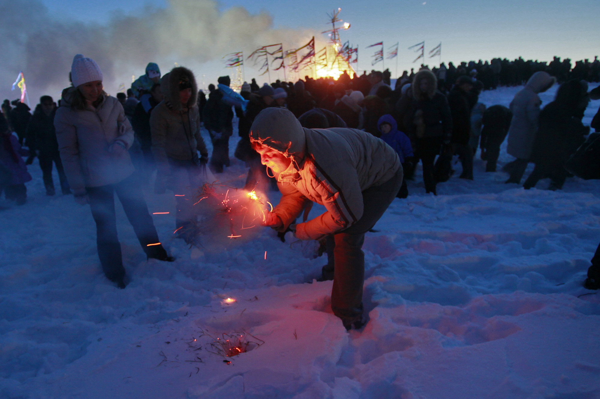 "A man tries to burn a small effigy of Lady Maslenitsa during the final evening of festivities in 2011 in St. Petersburg, Russia. The torching marks the end of the holiday -- a fiery goodbye to ""lady winter."" A larger straw effigy burns in the distance."