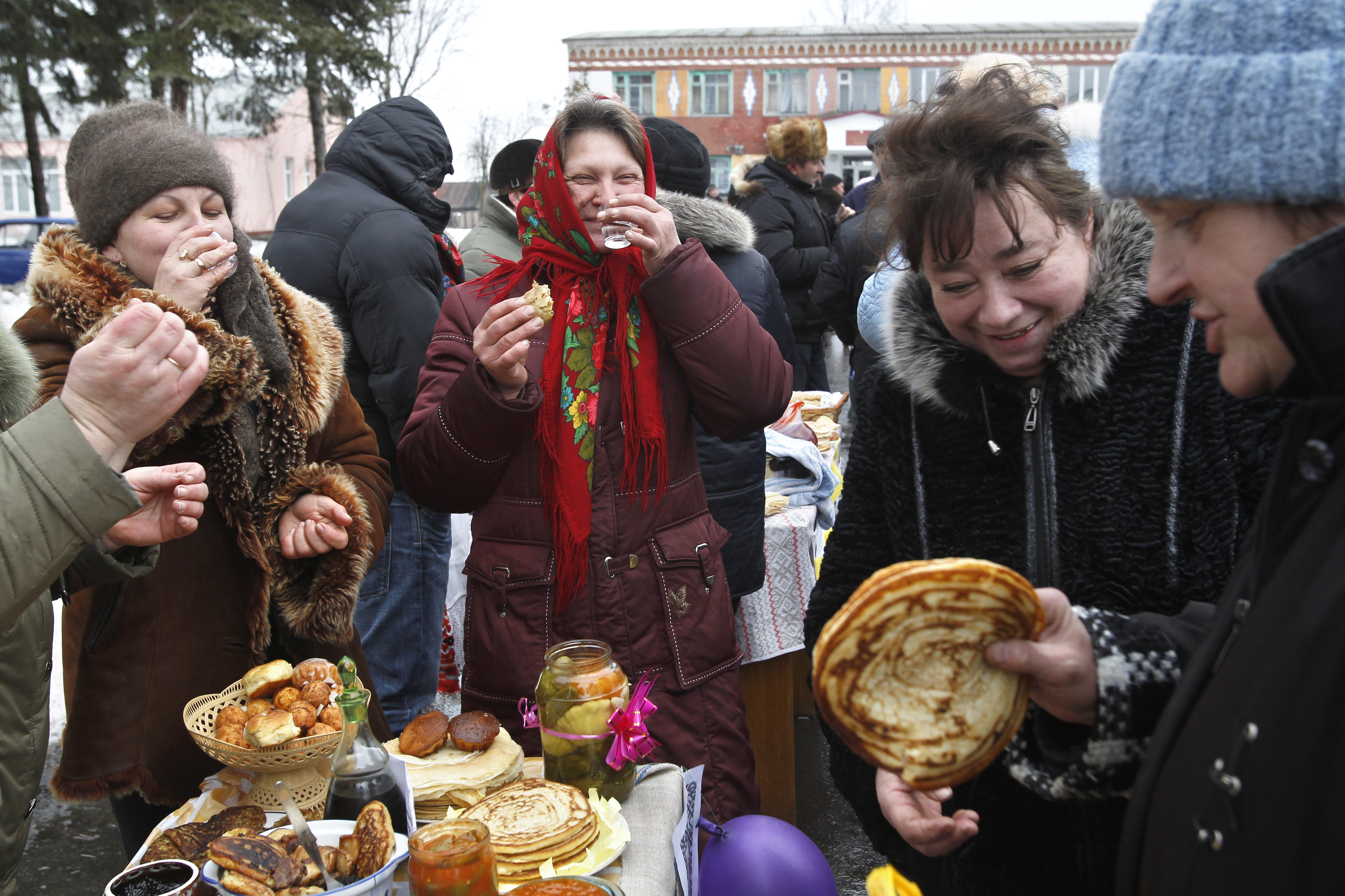 Belarusian woman drink vodka and sample more traditionally sized blinis.