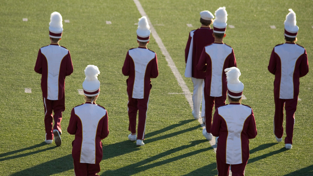 A marching band performs at halftime on the field during a high school football game.