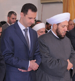 Syria's Grand Mufti Ahmad Hassoun (right) prays with President Bashar Assad in Damascus on Feb. 5, 2012. The grand mufti has called on Syrians to join the army and fight for the government, his most partisan statement since the country's uprising began two years ago.