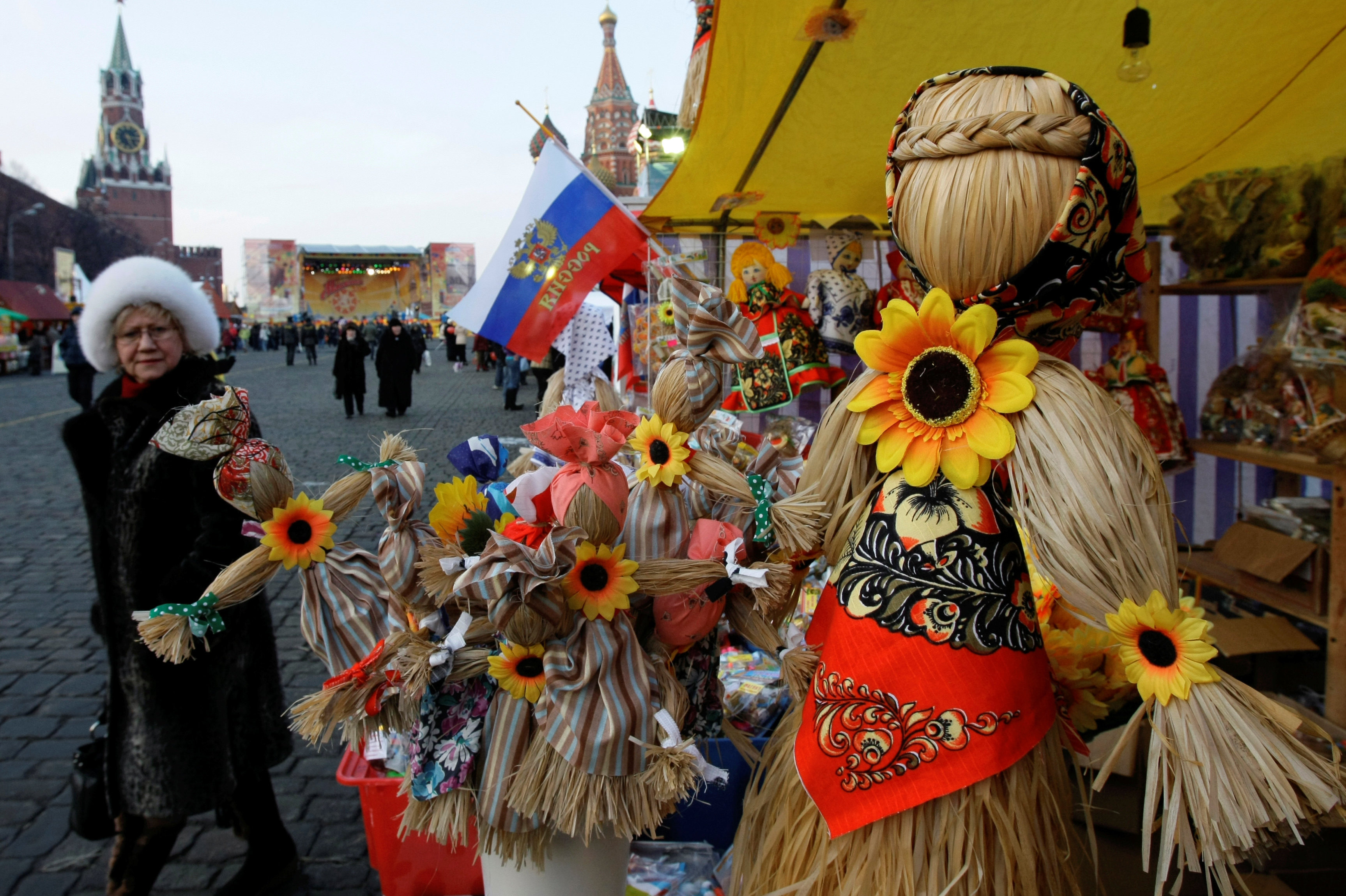 "People view straw effigies for sale at a booth just outside the Kremlin in 2009. Often referred to as ""Lady Maslenitsa,"" the straw figures are meant to symbolize winter (the word for winter in Russian is feminine)."