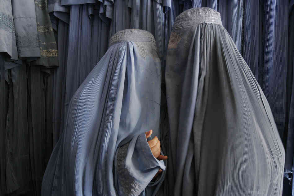 Two Afghan women clad in burqas whisper in a shop in Kabul, 2007. Despite advances in women's rights since the fall of the Taliban, most Afghan women, especially outside the capital, still opt for the all-enveloping cloak.