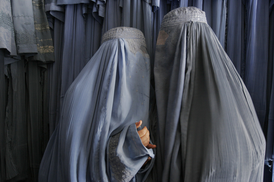 Two Afghan women clad in burqas whisper in a shop in Kabul, 2007. Despite advances in women's rights since the fall of the Taliban, most Afghan women, especially outside the capital, still opt for the all-enveloping cloak. (AP)