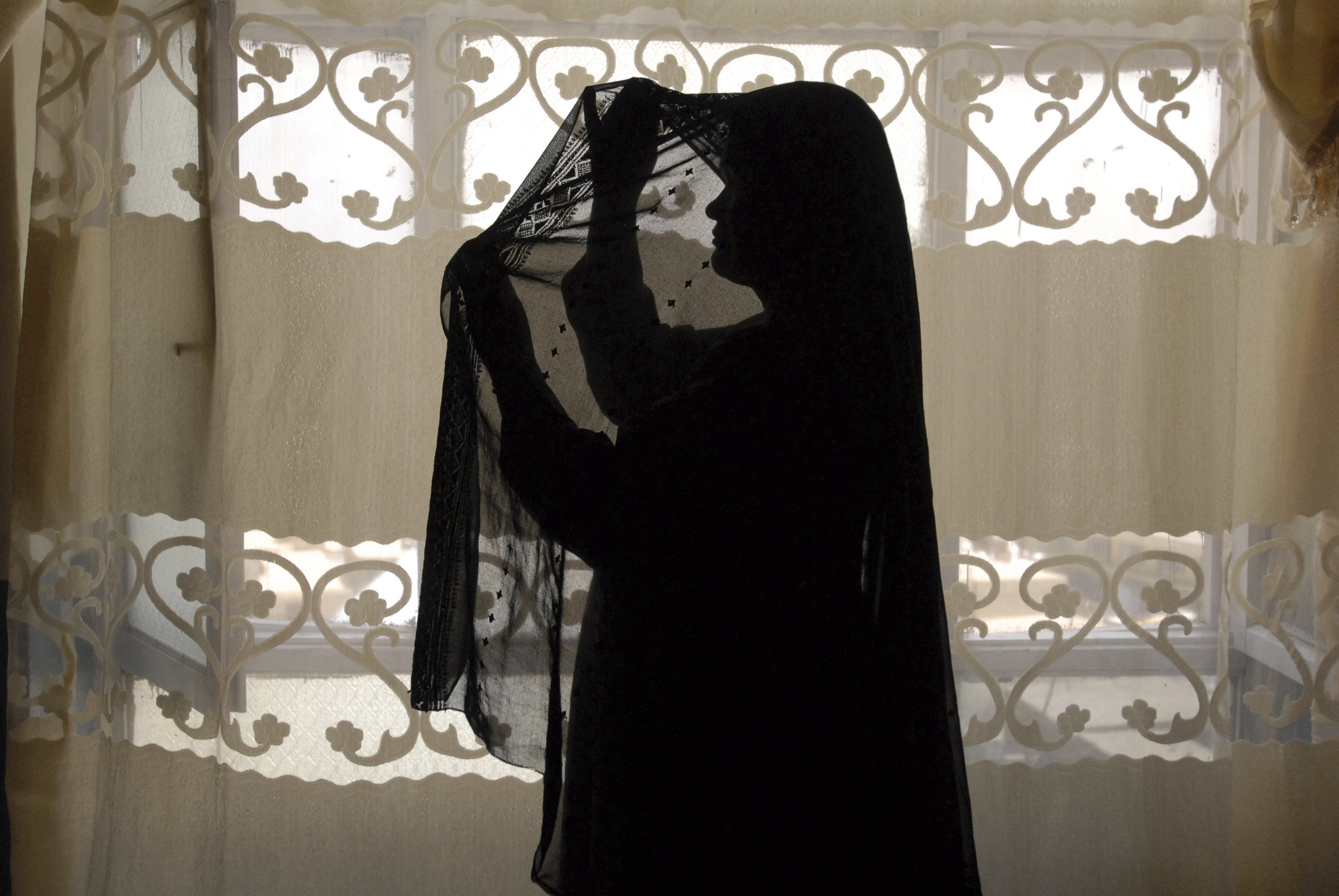 An unidentified Afghan prostitute fixes her headscarf to cover her face in Kabul, 2008. Afghanistan is one of the world's most conservative countries, yet its sex trade appears to be thriving.