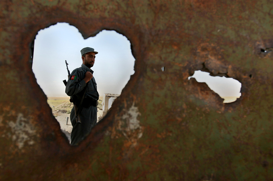 An Afghan policeman is seen through a hole at a police checkpoint on the outskirts of Kabul, 2007.