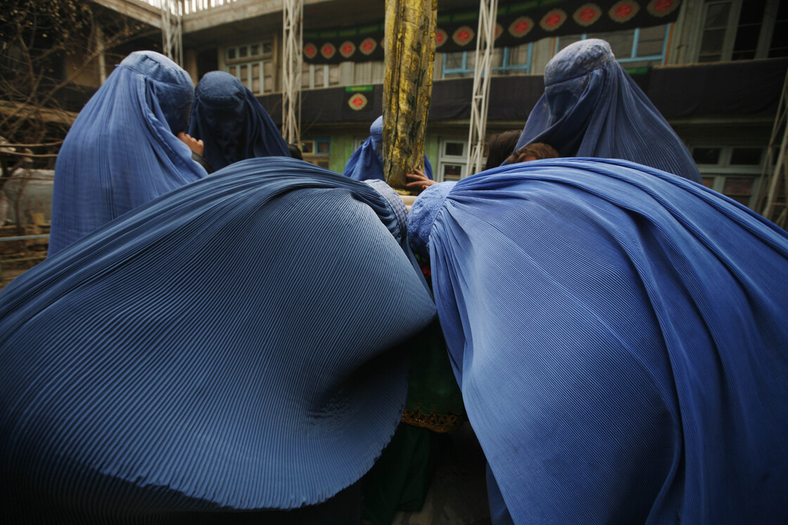 Afghan women kiss Shiite religious flags during Ashura in Kabul, 2009.