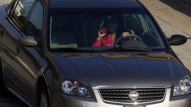 A woman uses a cellphone while driving in Los Angeles in 2011.