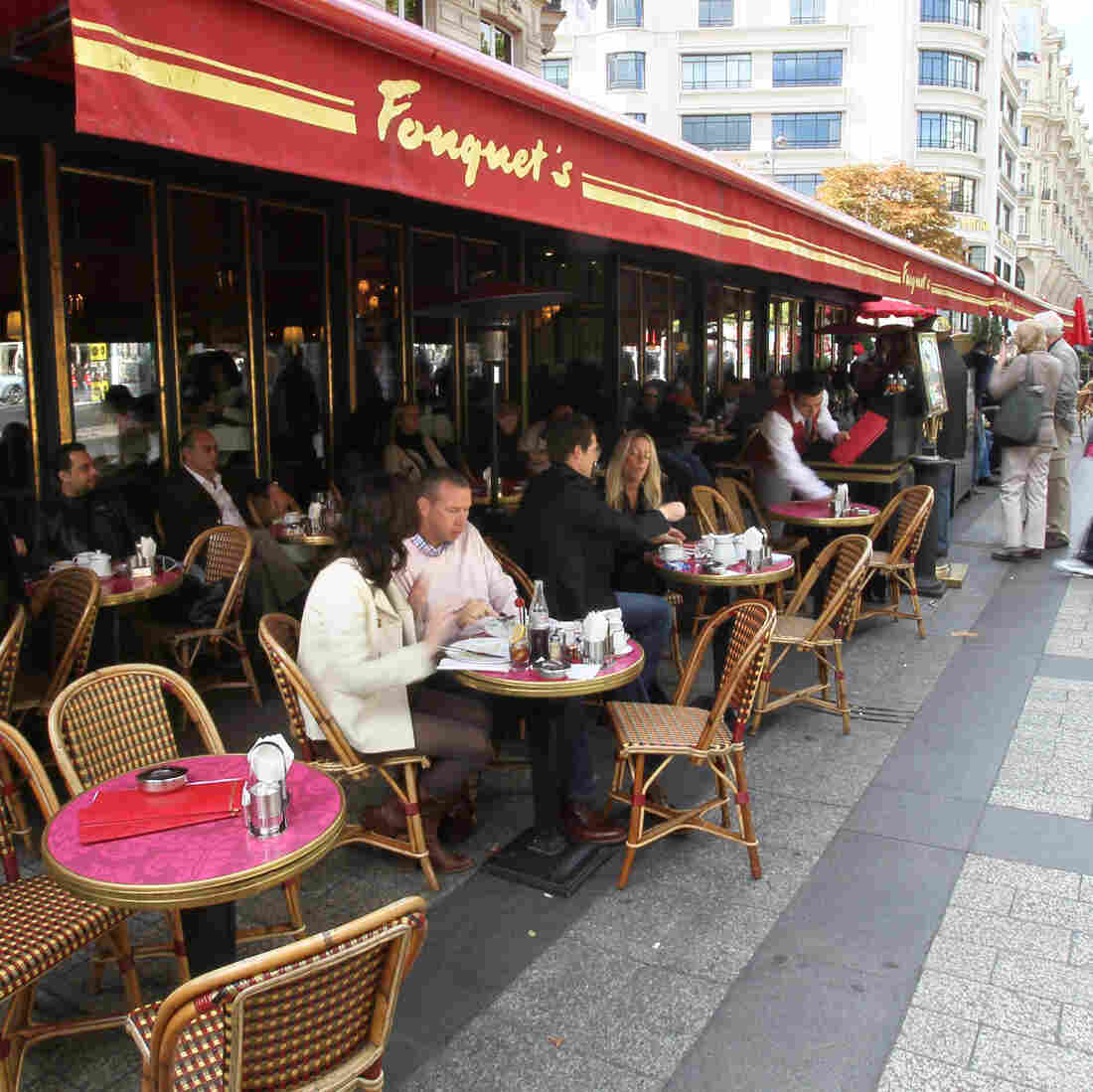 Diners eat at Fouquet's restaurant, a landmark on the Champs Elysees in Paris for more than a century. Traditional cafes and shops are steadily giving way to large global chains.