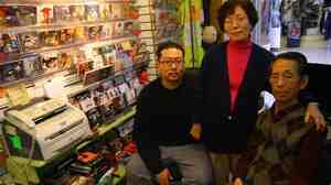 Wan Joon Kim (right), with his son Kirk and wife, Boo Ja, at their stall inside the Compton Swap Meet last January.