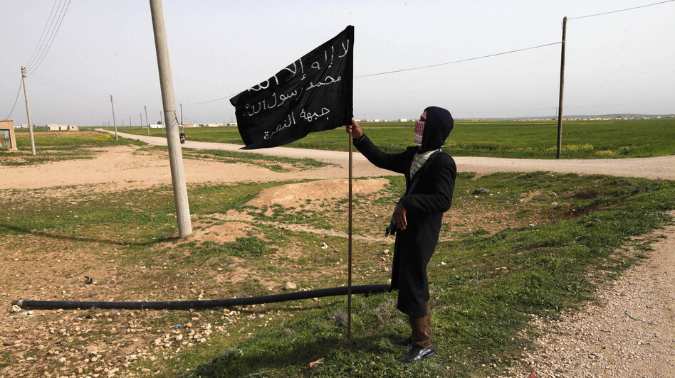 A member of an Islamist group holds a flag in Raqqa province, eastern Syria, on Tuesday. Recently, militants there posted leaflets announcing that anyone who supports democracy is an infidel — a serious offense under Shariah law. (Reuters/Landov)